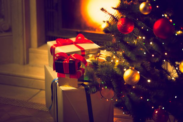 Christmas tree and gift boxes against burning fireplace
